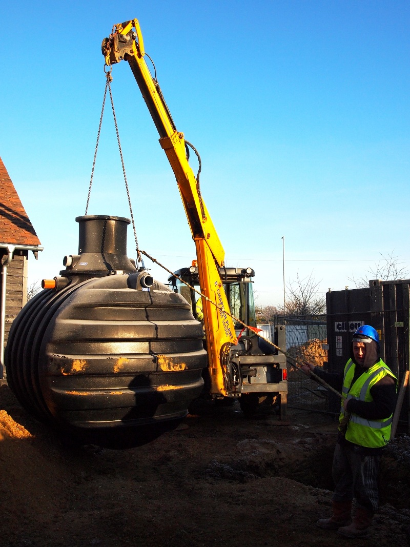 Easing a Kingspan Water Envireau rainwater harvesting tank into place